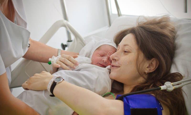 抱着新出生的婴孩的母亲 库存照片