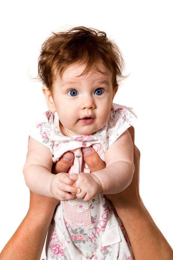 抱着看c有蓝眼睛的男性手的一个婴孩 库存照片