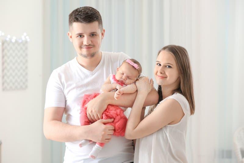 抱着逗人喜爱的睡觉的新出生的婴孩的愉快的年轻家庭在hom 免版税库存照片