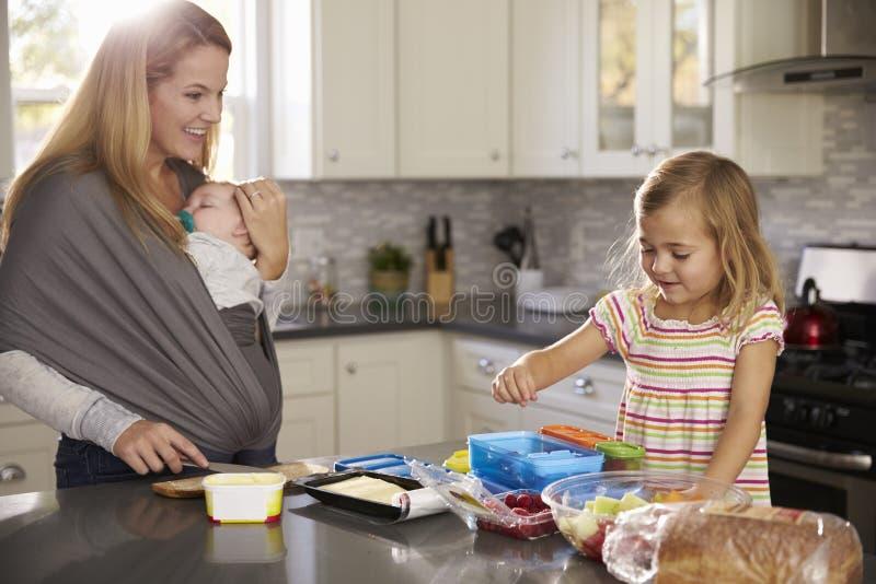 抱着婴孩的妈咪观看更老的女儿准备食物 库存图片