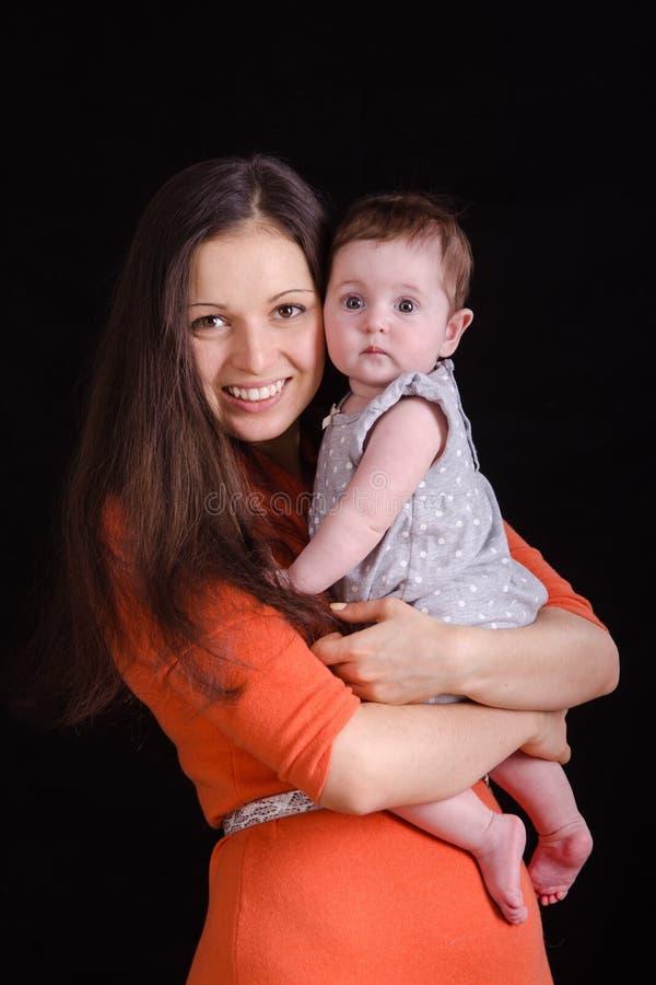 抱着婴孩的愉快的母亲 库存图片