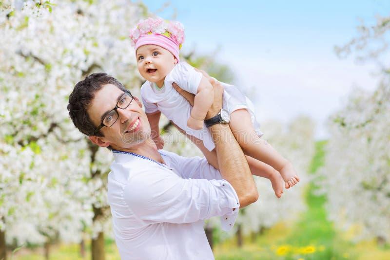 抱他心爱的孩子的快乐的父亲 免版税库存图片