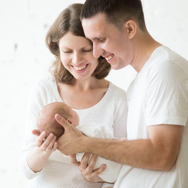 抱他们的孩子的愉快的父母 免版税库存照片