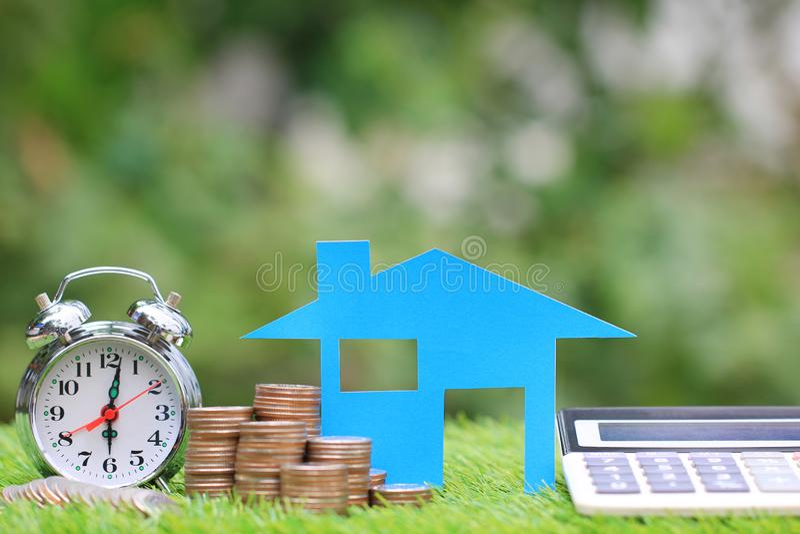 抵押计算器、蓝色房子模型和堆与闹钟的硬币金钱在自然绿色背景,利息和 免版税库存图片