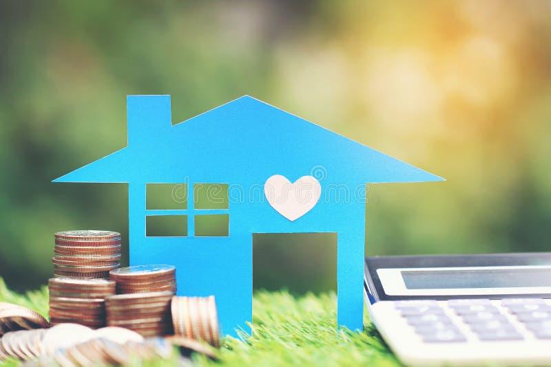 抵押计算器、蓝色房子模型和堆在自然绿色背景,利息和银行业务概念的硬币金钱 免版税库存图片