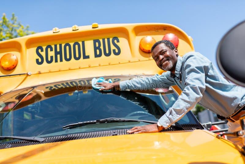 抹前窗学校班车和看的微笑的成熟非裔美国人的公交司机 图库摄影