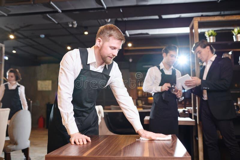 抹桌的有胡子的侍者在餐馆 免版税库存图片