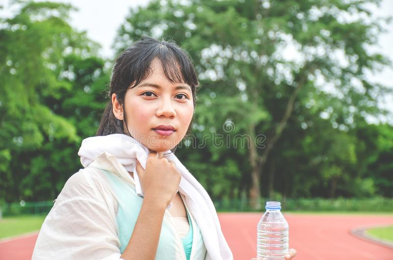 抹汗水和拿着一个瓶水的惊人的健身妇女在跑步户外在体育场以后在晴朗的早晨 免版税库存照片