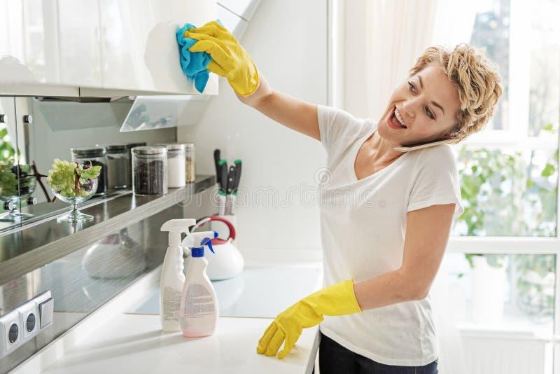 抹碗柜的健谈快乐的妇女 免版税库存照片