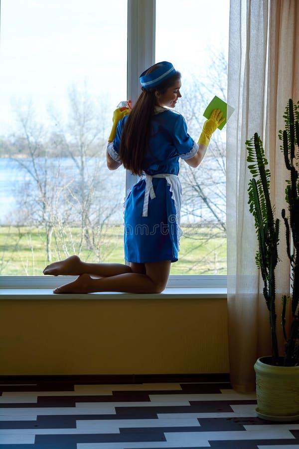抹窗口的可爱的年轻佣人 免版税库存照片