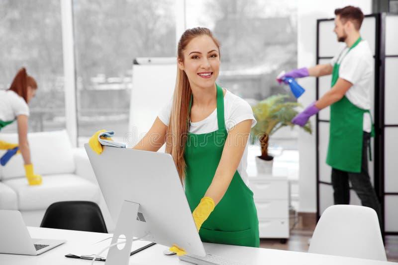 抹计算机的年轻女性擦净剂在办公室 库存照片
