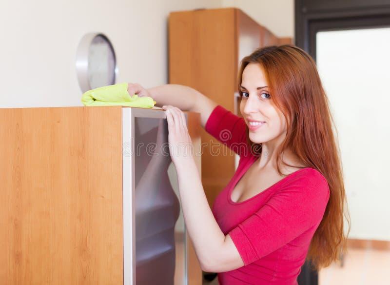 抹从家具的红发女孩尘土 免版税库存图片
