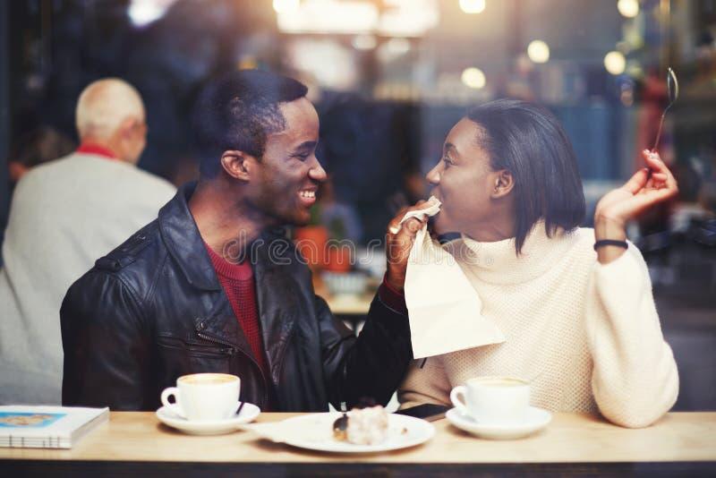 抹嘴的微笑的男朋友与餐巾他的女朋友在现代咖啡店内部的早餐期间 免版税库存图片