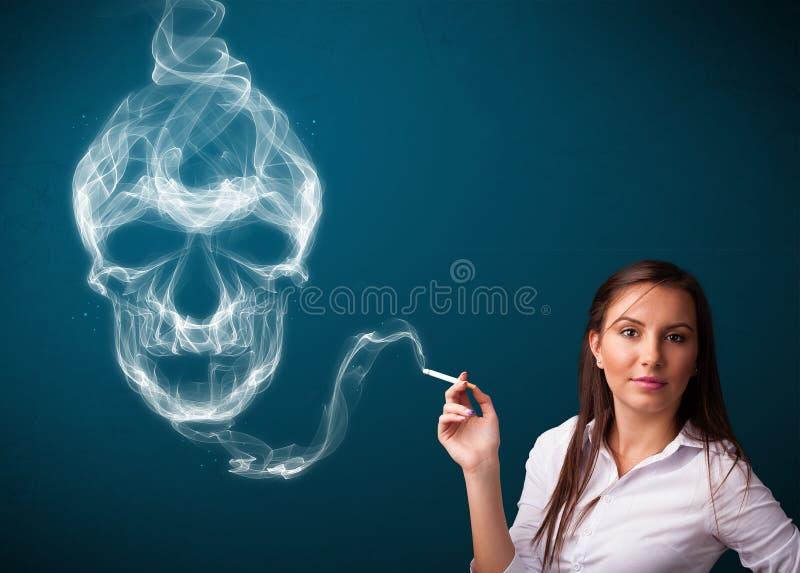 抽与毒性头骨烟的少妇危险香烟 库存照片