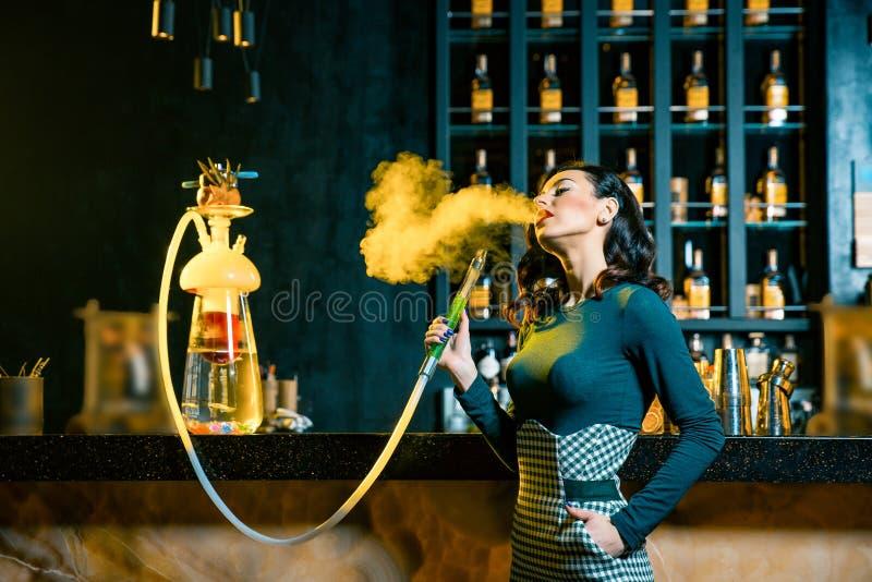 抽在酒吧后的少妇水烟筒 烟云 享用水烟筒的少妇秀丽画象 免版税库存照片