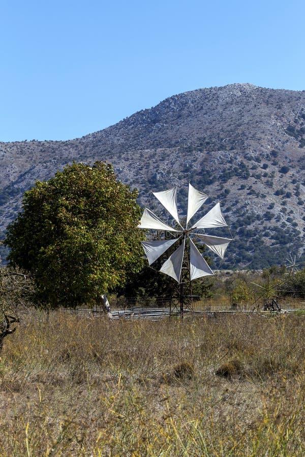 抽水出于领域灌溉的地面在好日子Lassithi地区的老,历史,著名,金属风车 免版税库存图片