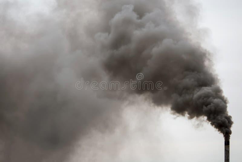 抽烟工厂的烟囱,在天空的重的黑烟 免版税库存照片