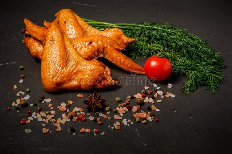 抽烟的鸡翅用新鲜的莳萝、蕃茄和香料 免版税库存图片