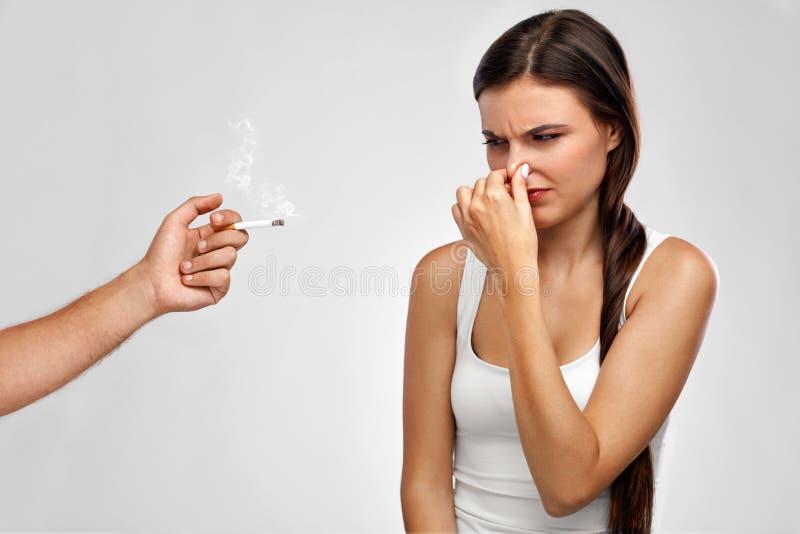 抽烟 握鼻子,嗅到的香烟气味的美丽的妇女 免版税库存图片