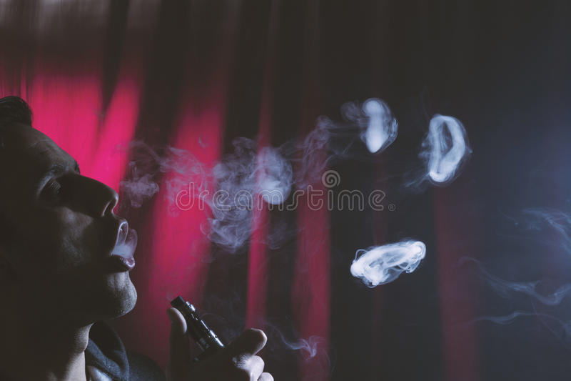 抽电子香烟或e香烟的年轻人 免版税库存图片