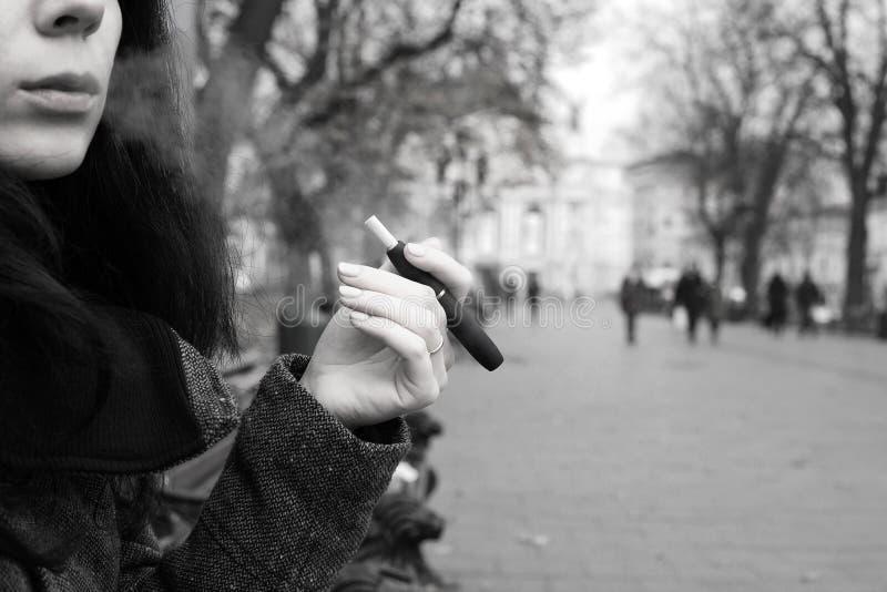 抽电子香烟,Iqos的女孩,黑&白色 库存照片