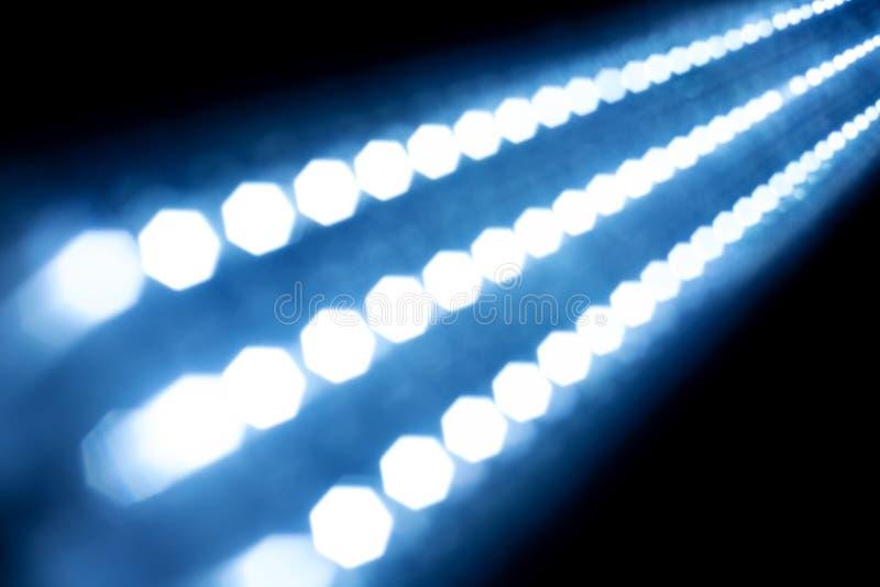 抽象在黑背景的纹理发光的光 被弄脏的轻的小条 蓝色焕发 许多小发光的电灯泡 图库摄影