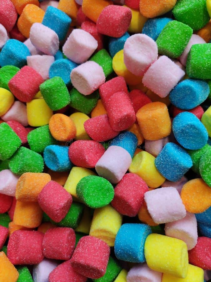 抽象多彩多姿的蛋白软糖背景,在糖,呈杂色的纹理充分的空间的红色黄色蓝绿色甜软的圆筒, 免版税库存照片