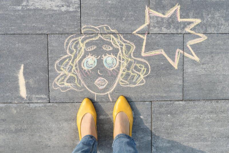 抽象流行艺术妇女面孔,在灰色边路写的图片在蜡笔,有妇女腿的在黄色鞋子 免版税库存照片