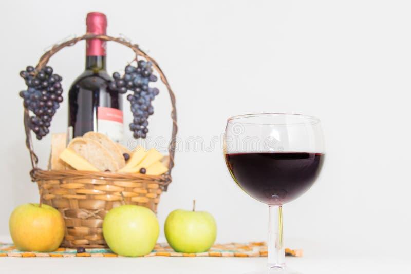 抽象玻璃图象酒 一个瓶红葡萄酒、葡萄和野餐篮子用乳酪和面包切片 免版税库存照片