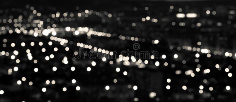 抽象白色黑圆bokeh背景,城市在t点燃 免版税库存照片