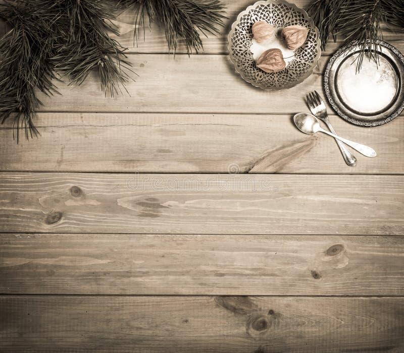 抽象空白背景圣诞节黑暗的装饰设计模式红色的星形 古色古香的木桌、杉木分支和葡萄酒项目 银色盘子、叉子和匙子,栓与一把桃红色弓 复制 免版税库存图片