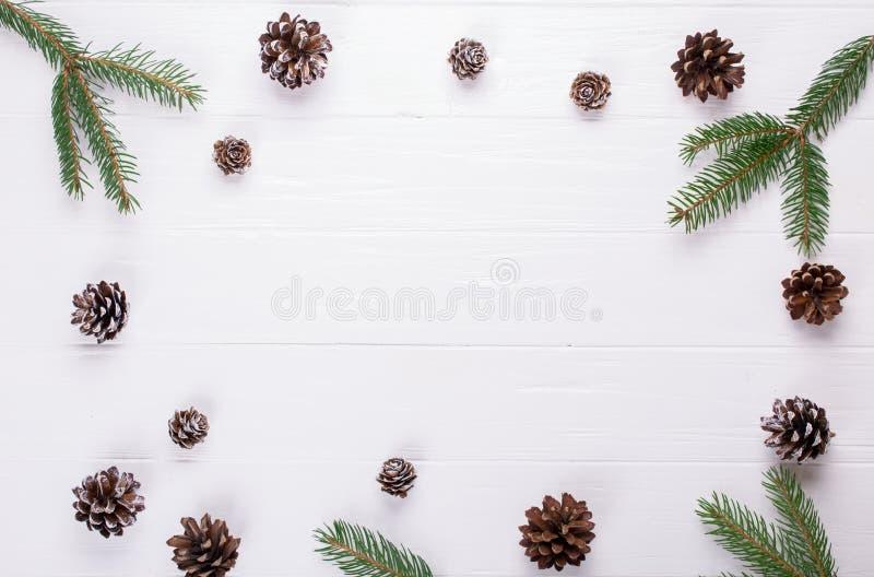 抽象空白背景圣诞节黑暗的装饰设计模式红色的星形 圣诞节框架在白色trable做了杉树分支和杉木锥体装饰土气元素 图库摄影