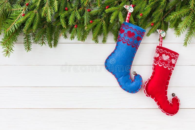 抽象空白背景圣诞节黑暗的装饰设计模式红色的星形 圣诞节与装饰,红色和蓝色圣诞节袜子的杉树在白色木背景,拷贝 库存图片