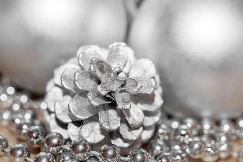 抽象背景圣诞节银 特写镜头色的杉木锥体、螺纹与小珠和被弄脏的球在背景中 库存照片