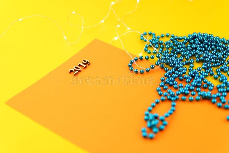 抽象背景圣诞节 在与蓝色小珠的黄色背景是与第的一张卡片2019年 免版税库存图片