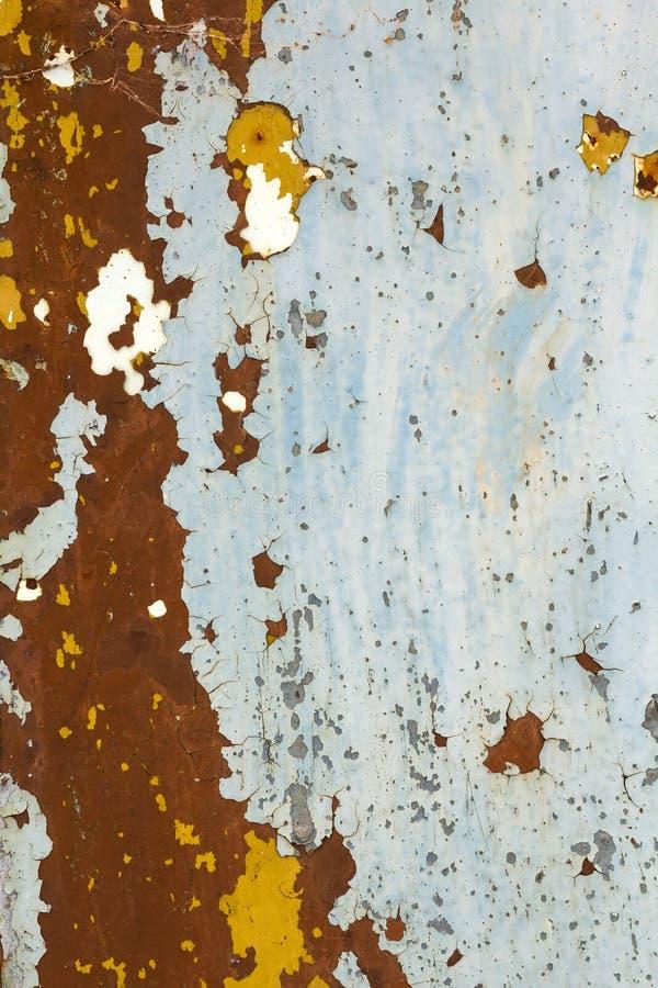 抽象背景纹理垂直脏生锈金属片与削皮油漆和广泛的腐蚀与铁锈斑纹 免版税库存照片