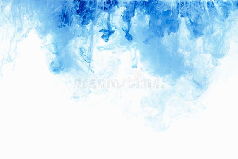 抽象背景颜色墨水下落在水中 油漆蓝色云彩在白色的 免版税库存照片