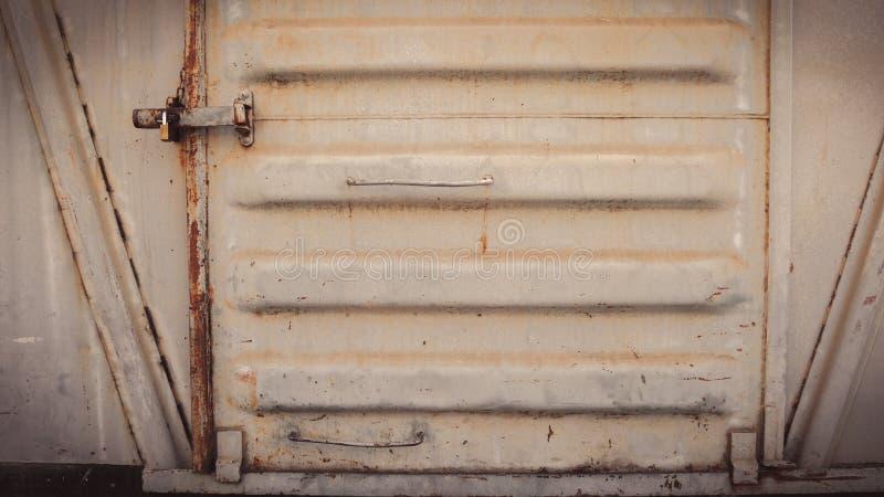 抽象脏的金属表面和锁在餐车的生锈的铁门训练 免版税库存图片