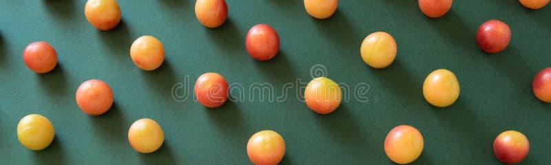 抽象食物样式 在绿色背景的未加工的李子果子 免版税库存图片
