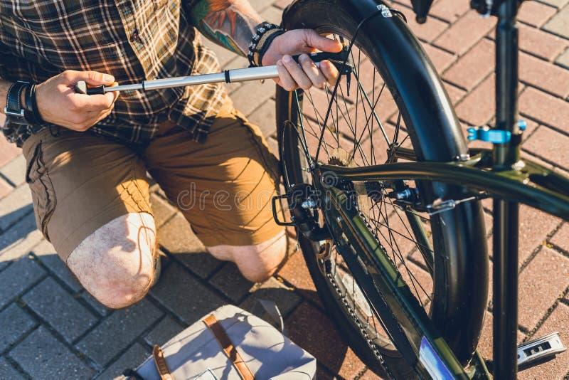 抽轮子自行车的无法认出的人手,为旅行做准备,维护运输概念 免版税库存图片