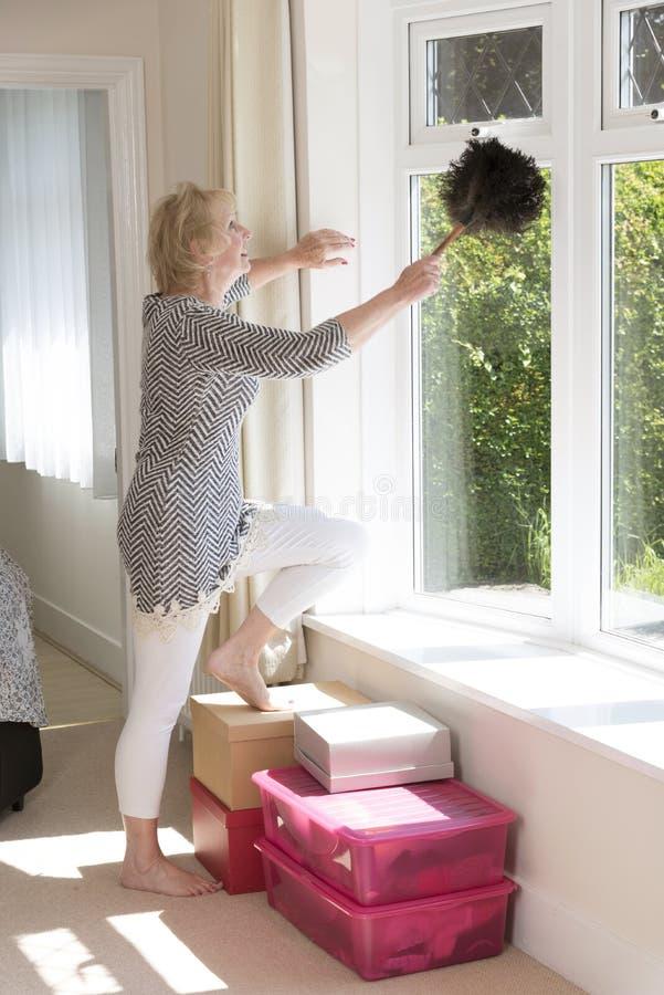 拂去窗架的灰尘妇女 图库摄影