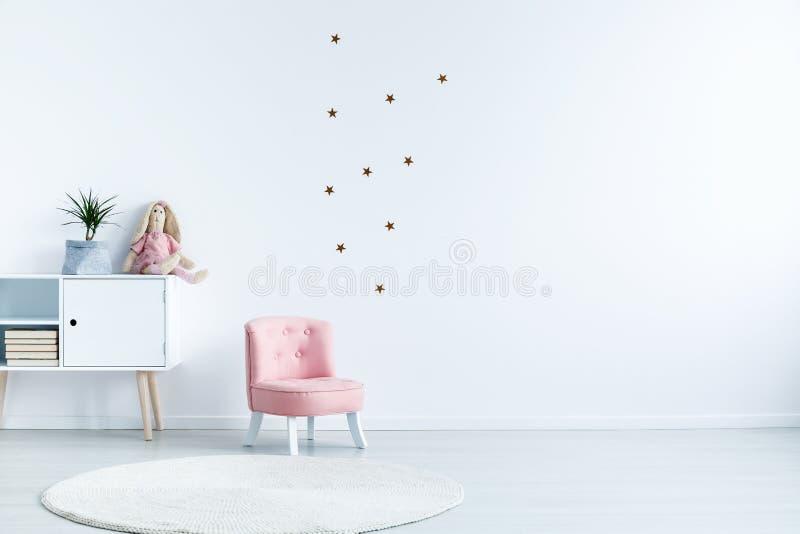 担任主角在白色墙壁上的贴纸有在儿童` s室inte的拷贝空间的 图库摄影