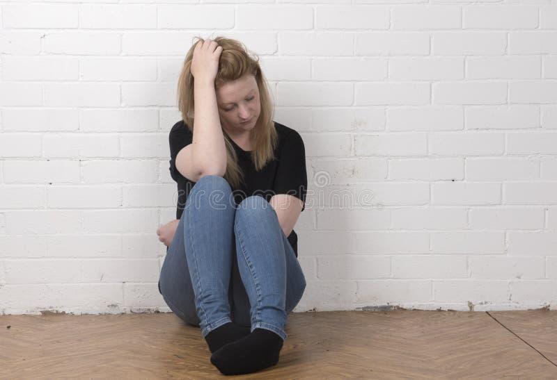 担心和害怕的年轻女性开会对一个白色砖墙 库存照片