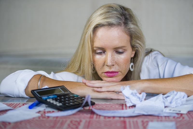 担心和绝望白肤金发的做文书工作和银行帐单的妇女计算的国内金钱费用认为与计算器su 库存照片
