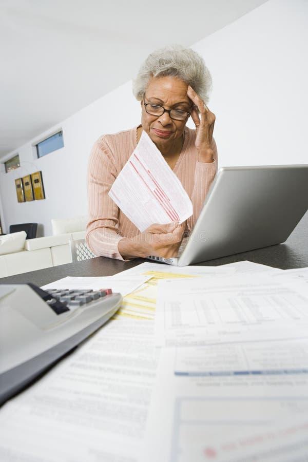 担心家庭财务的资深妇女 图库摄影
