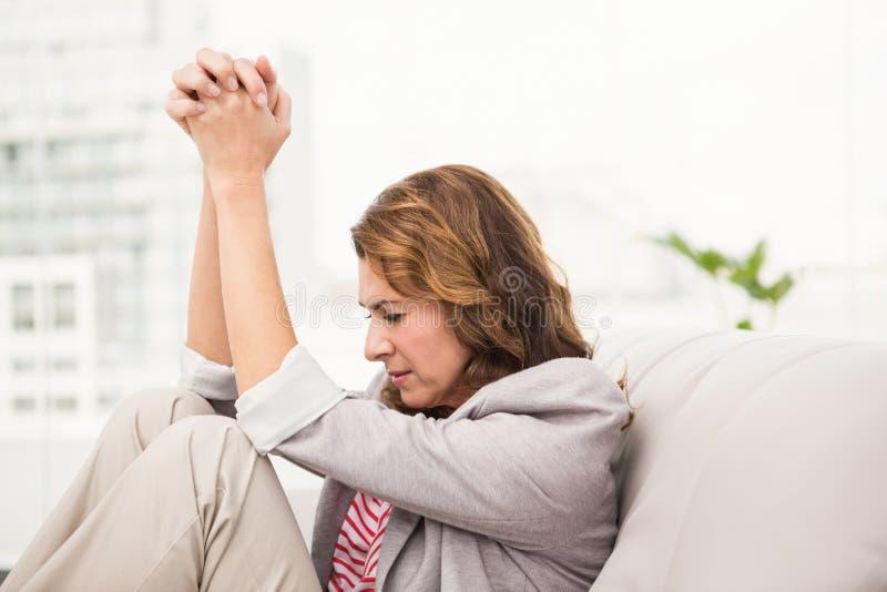 担心的偶然女实业家坐长沙发 免版税库存图片