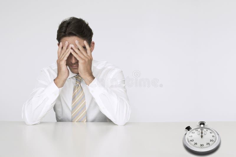 担心的商人在与代表时间损失的秒表的桌上 免版税图库摄影