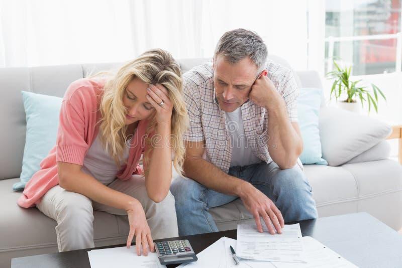 担心的在长沙发的夫妇计算的票据 库存图片