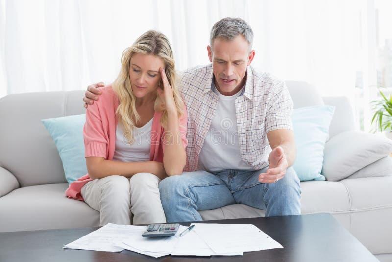 担心的在长沙发的夫妇计算的票据 免版税库存图片