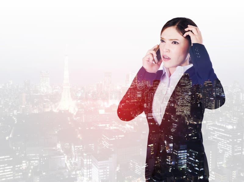 担心的女商人两次曝光谈话在有城市的智能手机 库存照片